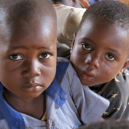 Afrikanische Jungen schauen mit großen Augen in die Kamera. Auch sie spüren die Auswirkungen von Corona.